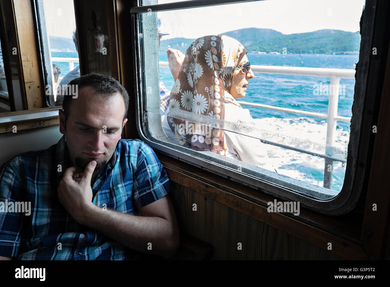 Passengers relaxing on a ferry that is travelling along the Bosphorus in Istanbul, Turkey Stock Photo
