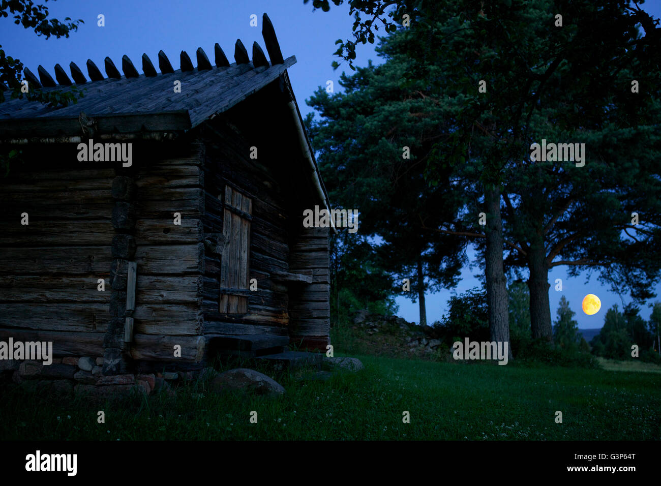 Sweden, Dalarna, Solleron, Wooden hut and moon in background Stock Photo