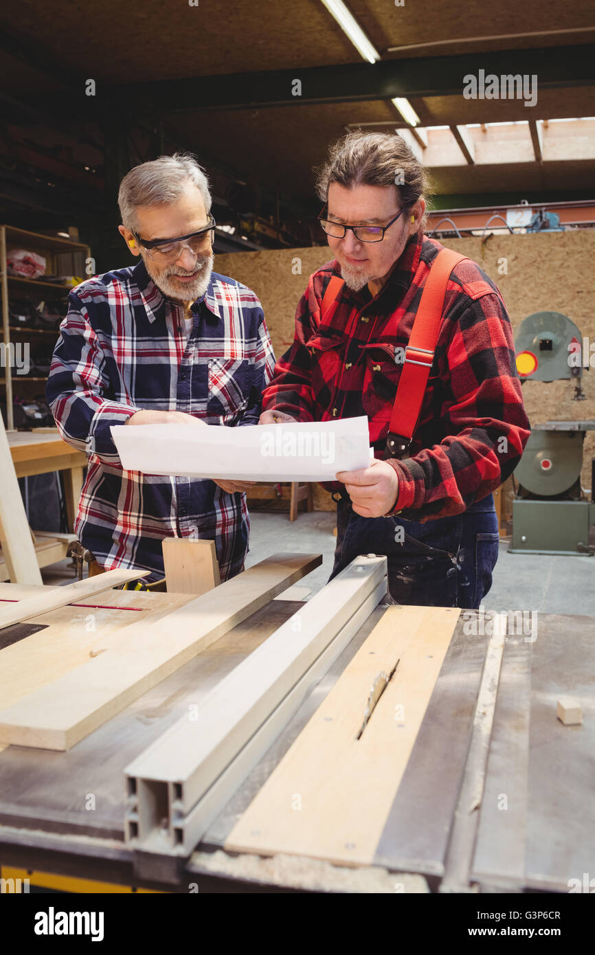Duo of carpenters studying plans - Stock Image