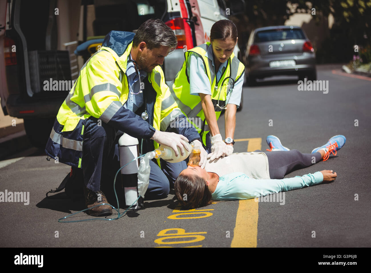 Jogger lying on the road taking in hand by ambulance crew - Stock Image