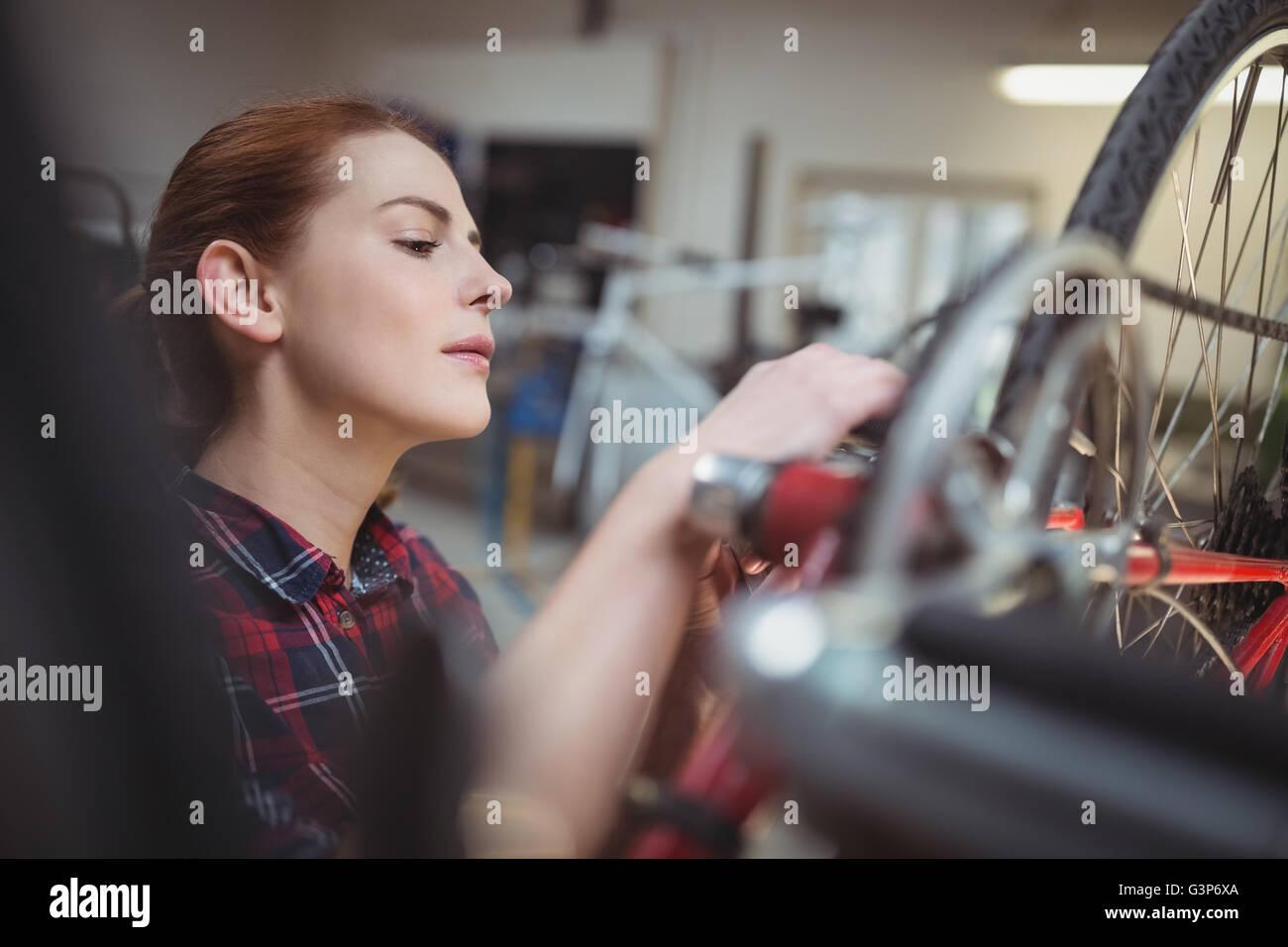 Female mechanic repairing a bicycle - Stock Image