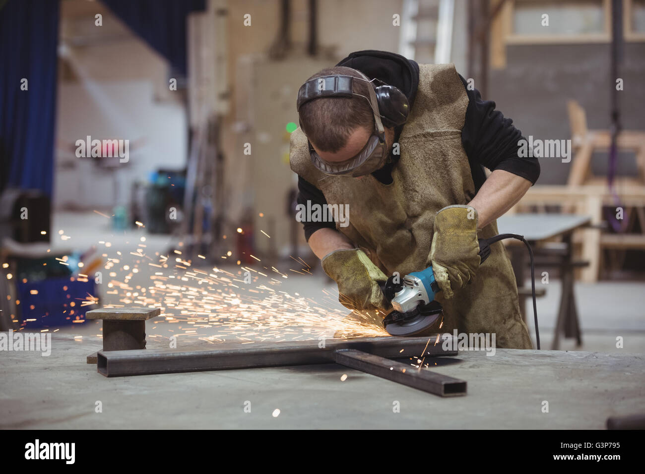 Worker using an angle grinder - Stock Image