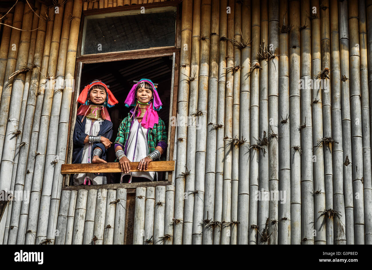 Women of the Kayan Lahwi tribe wearing traditional metal rings on their necks welcome visitors Stock Photo