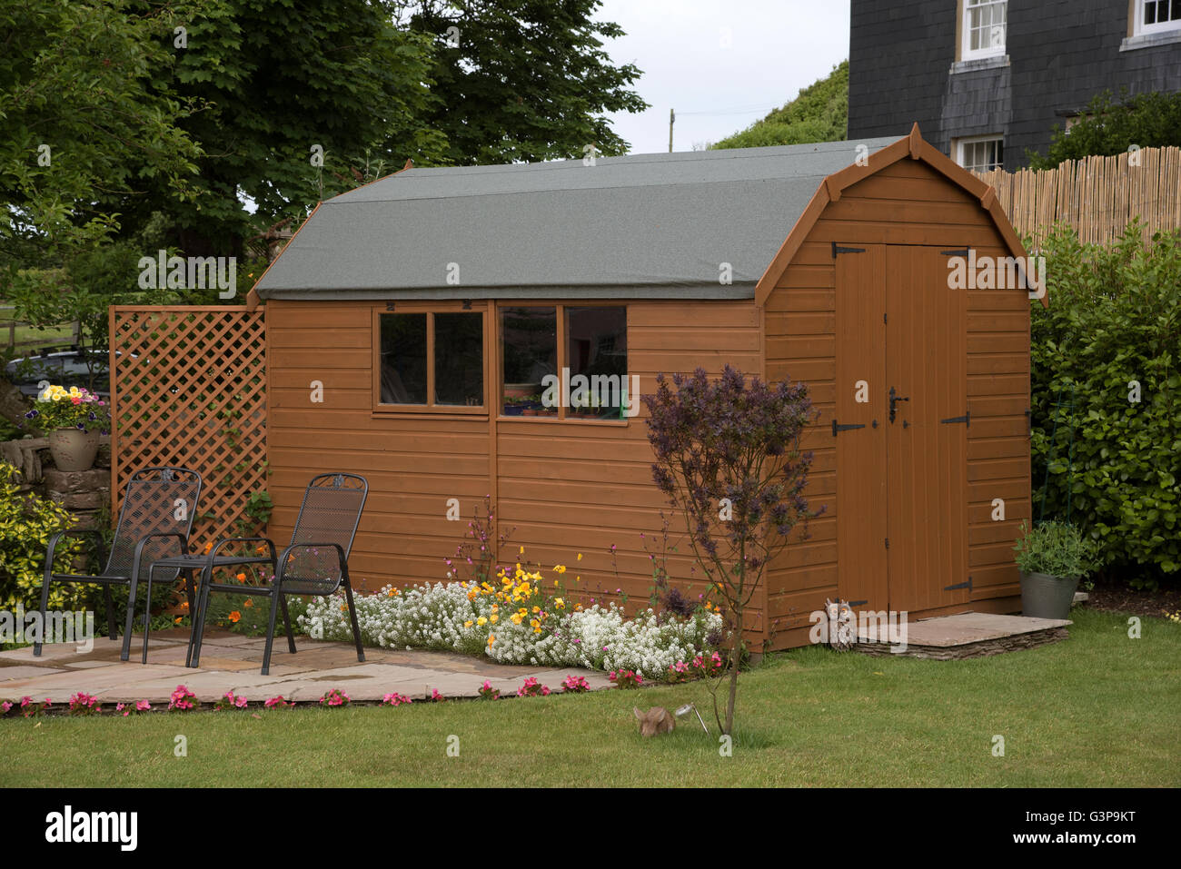 DEVON ENGLAND UK A barn style garden shed with a small patio and ...