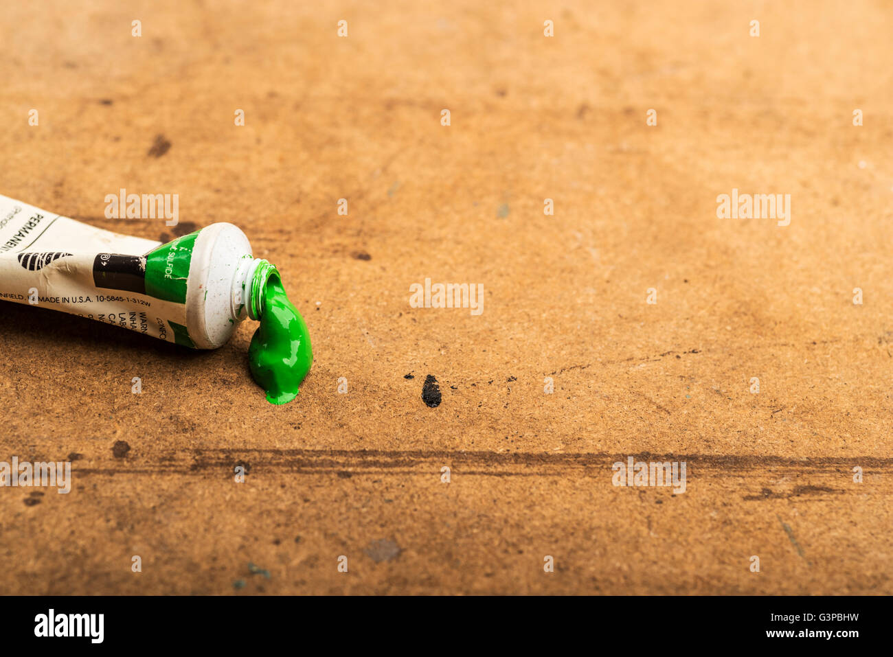 Tube of green acrylic paint on an artist's table. - Stock Image