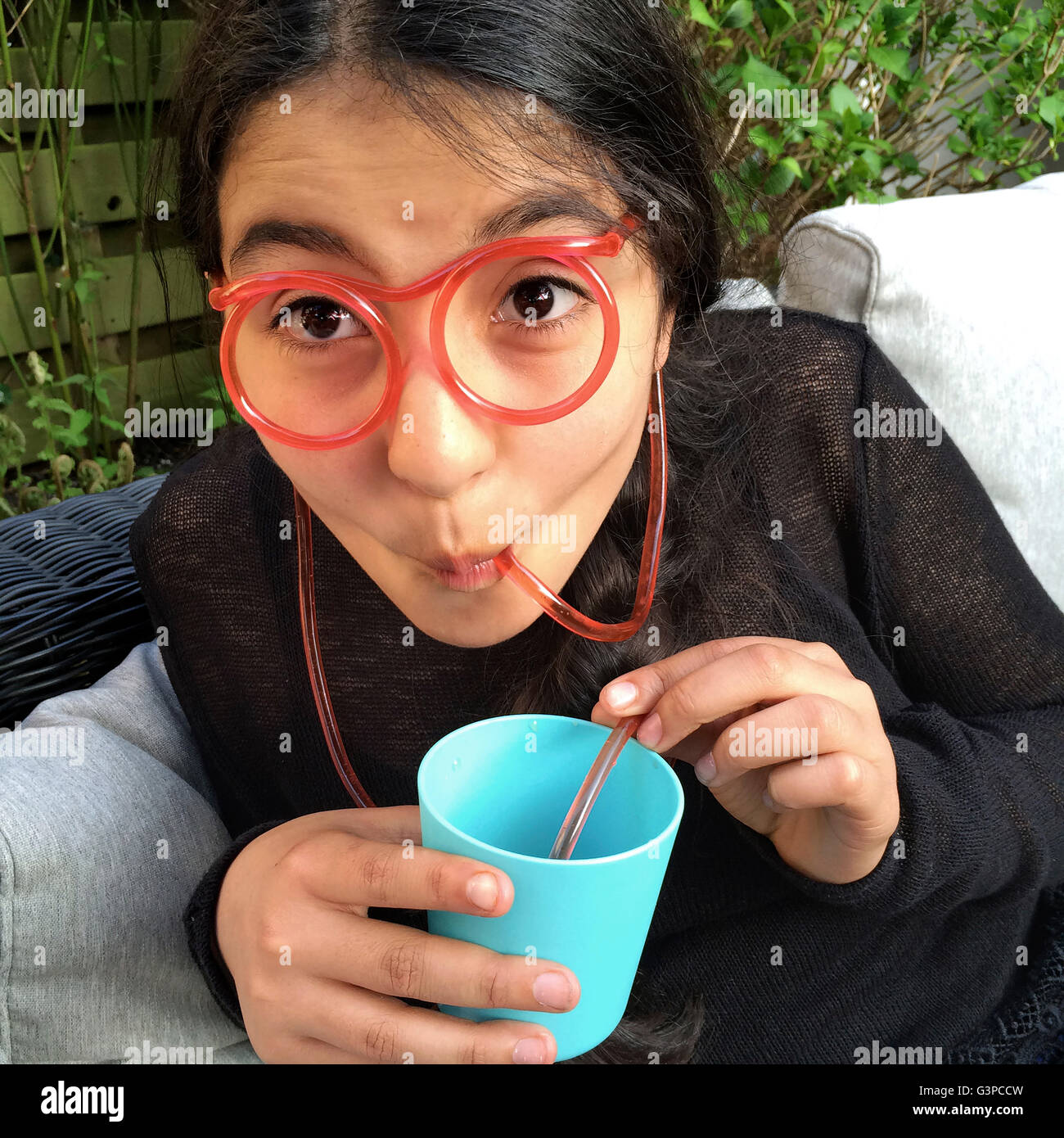 Teenage girl is drinking lemonade with a funny straw in the shape of glasses - Stock Image