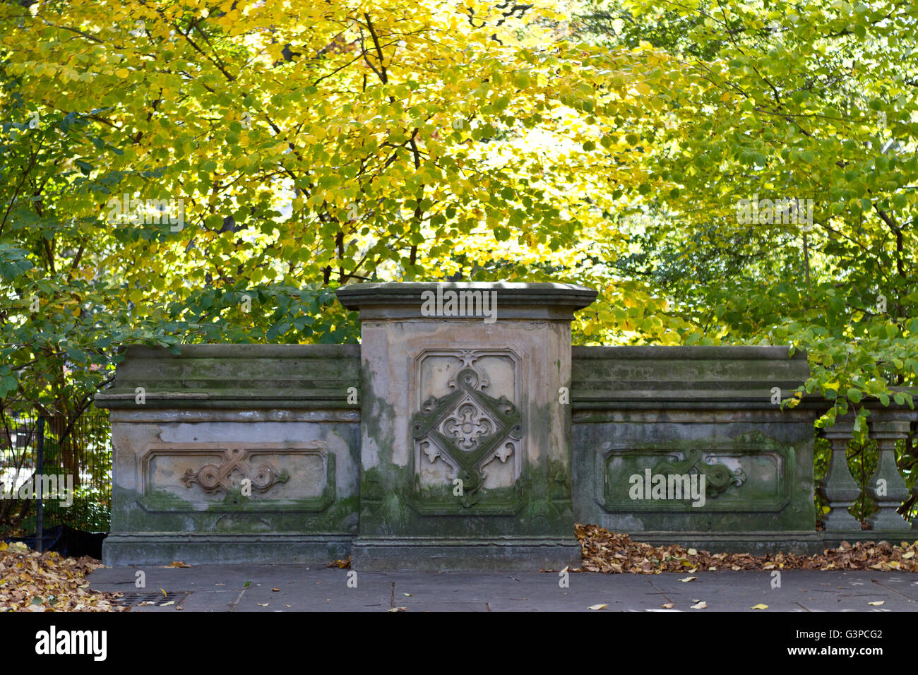 Architectural detail of a walking bridge with green patina surrounded by autumn foliage in Central Park - Stock Image