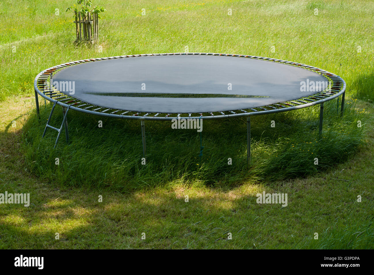 Torn trampoline mat. Polypropylene bed for a trampoline that has split with age and usage. - Stock Image