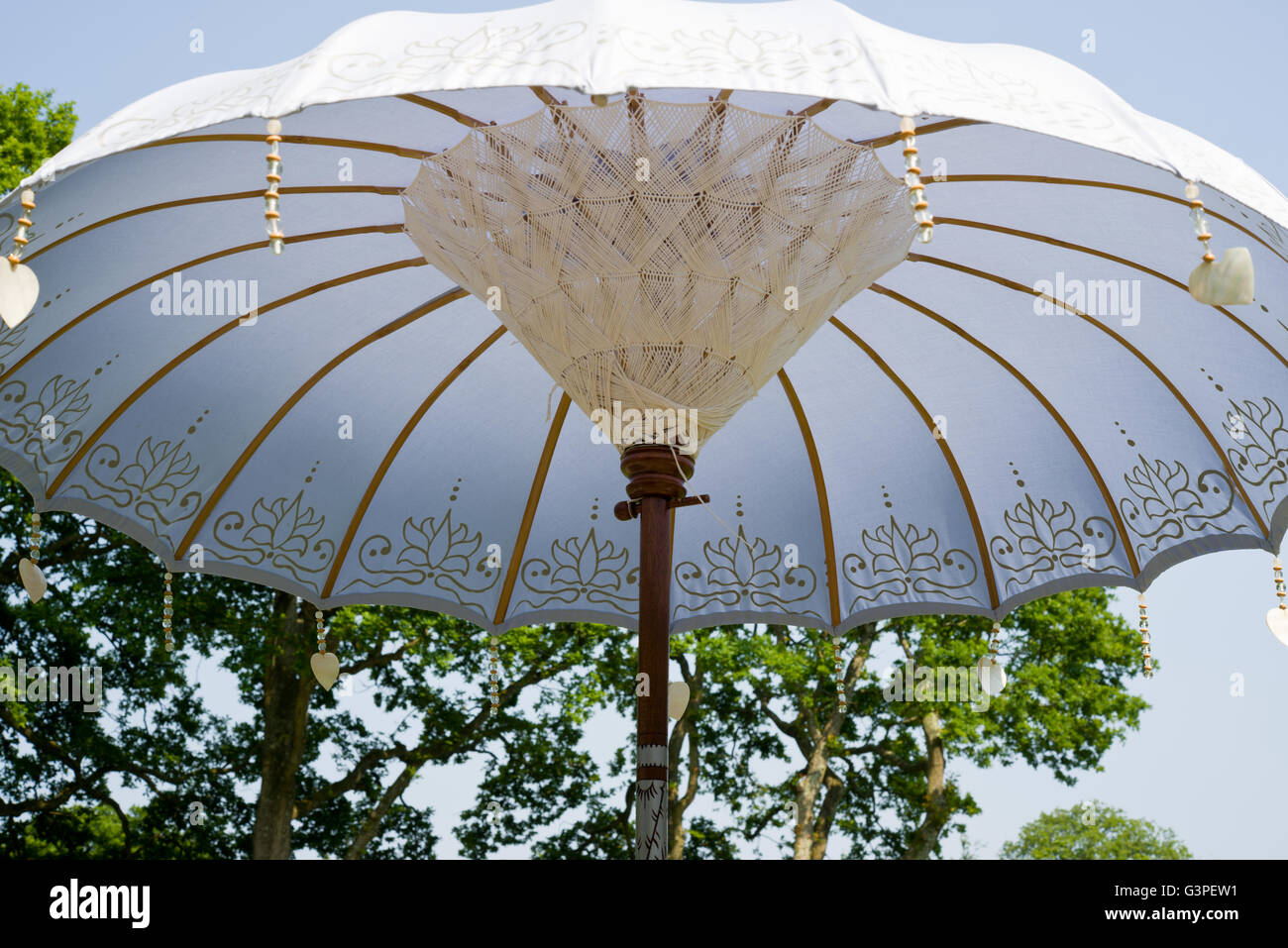 Garden sun umbrella or shade. Far Eastern decorative effects and shell hearts hanging pendants. - Stock Image