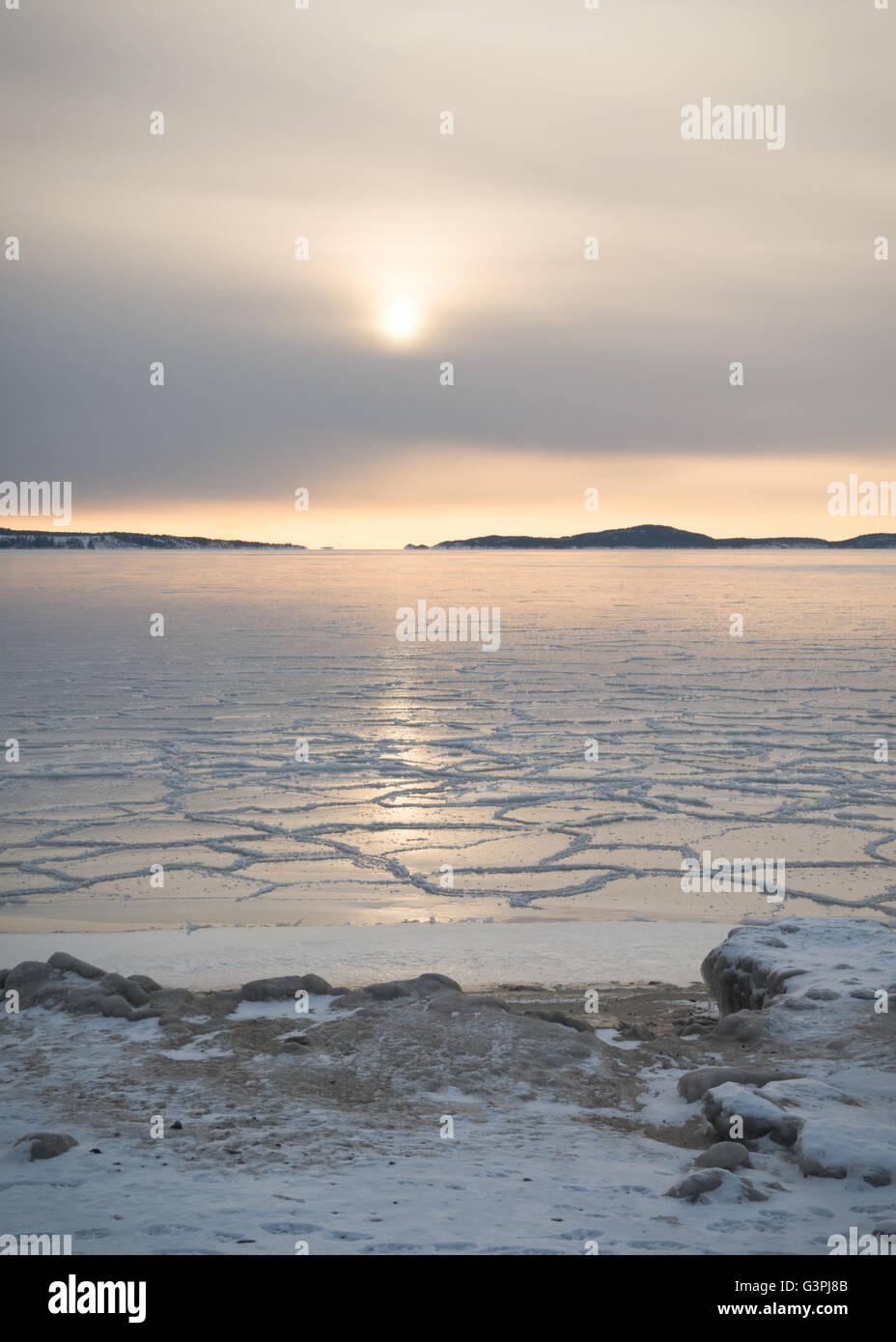 Low set sun reflecting in sea ice near the shore in the archipelago outside Örnsköldsvik in the northern - Stock Image