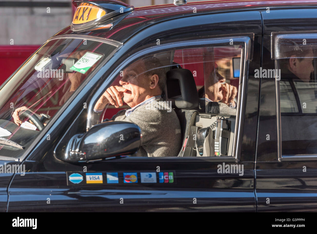 A black cab driver sitting in sunlight in busy traffic in London with a male passenger behind him. The taxi has - Stock Image