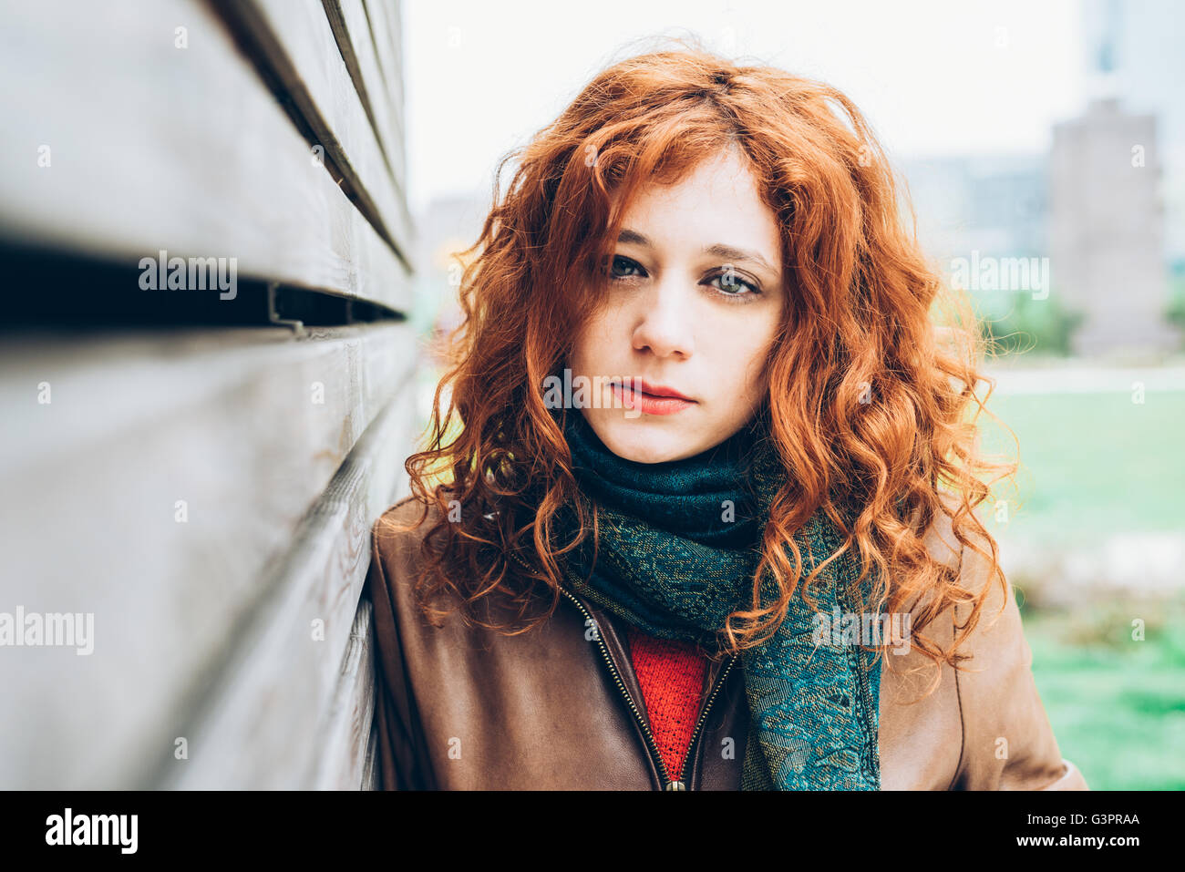 Half length portrait of young beautiful caucasian redhead woman looking in camera, pensive - intense, thoughtful, - Stock Image