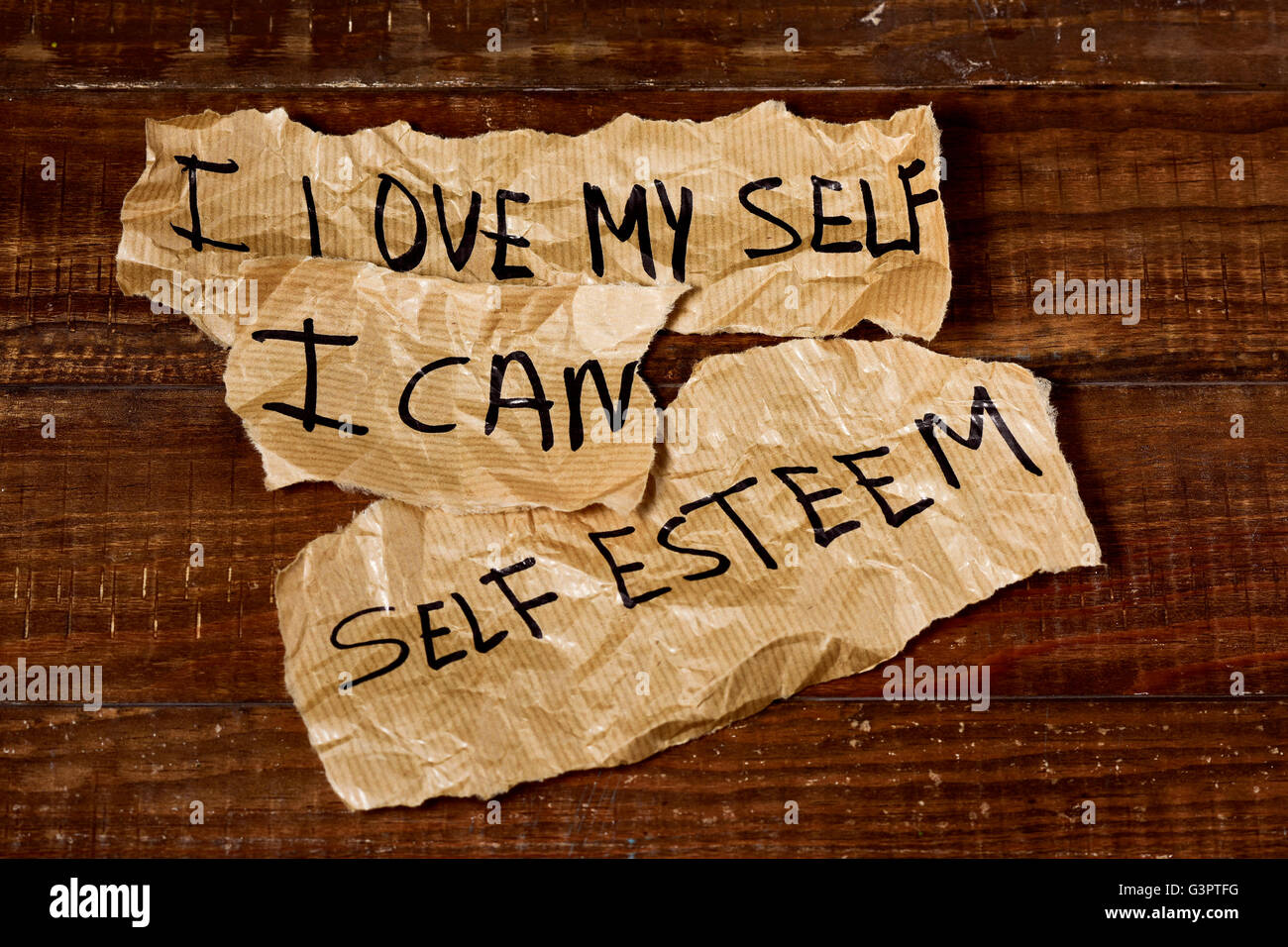 the text I love myself, I can and self esteem written in some pieces of paper, placed on a rustic wooden surface - Stock Image