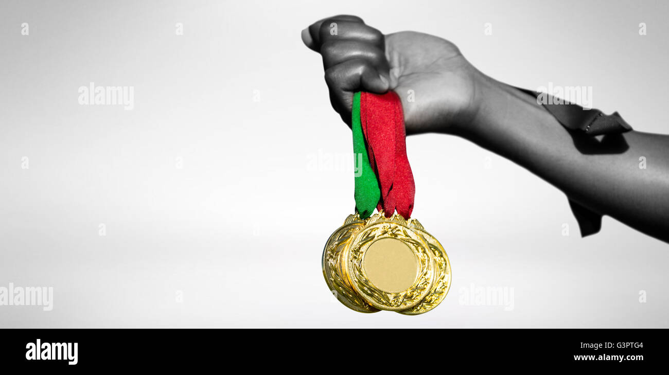 View of hand holding three gold medals - Stock Image