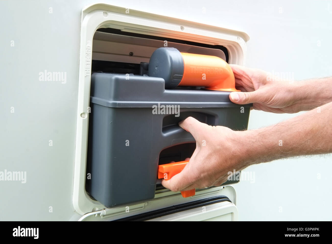 Thetford Cassette Toilet : Man removing a thetford cassette toilet from a motorhome stock