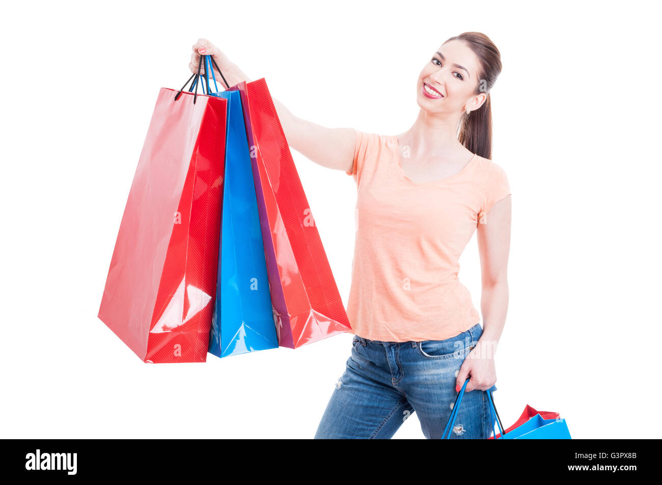 Beautiful young woman holding few shopping bags, smiling and feeling satisfied or content isolated on white background Stock Photo