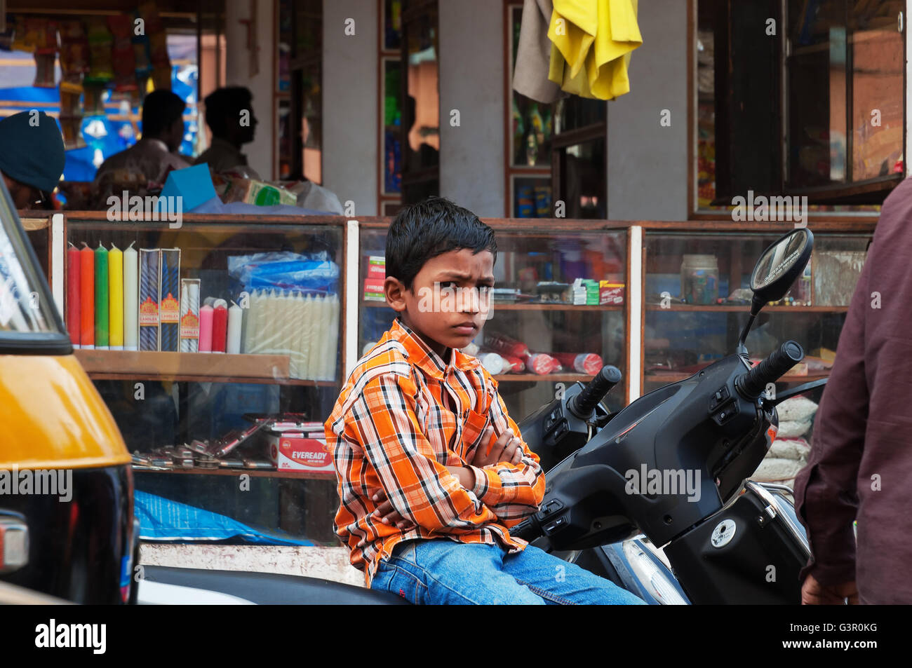 Unidentified Indian young boy sitting on the bike at the Russell market. Russell Market - Stock Image