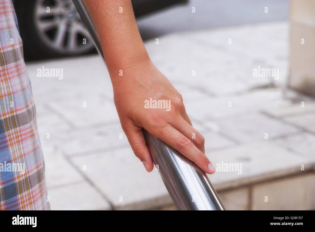 Woman hand using handrail. Urban scene. - Stock Image