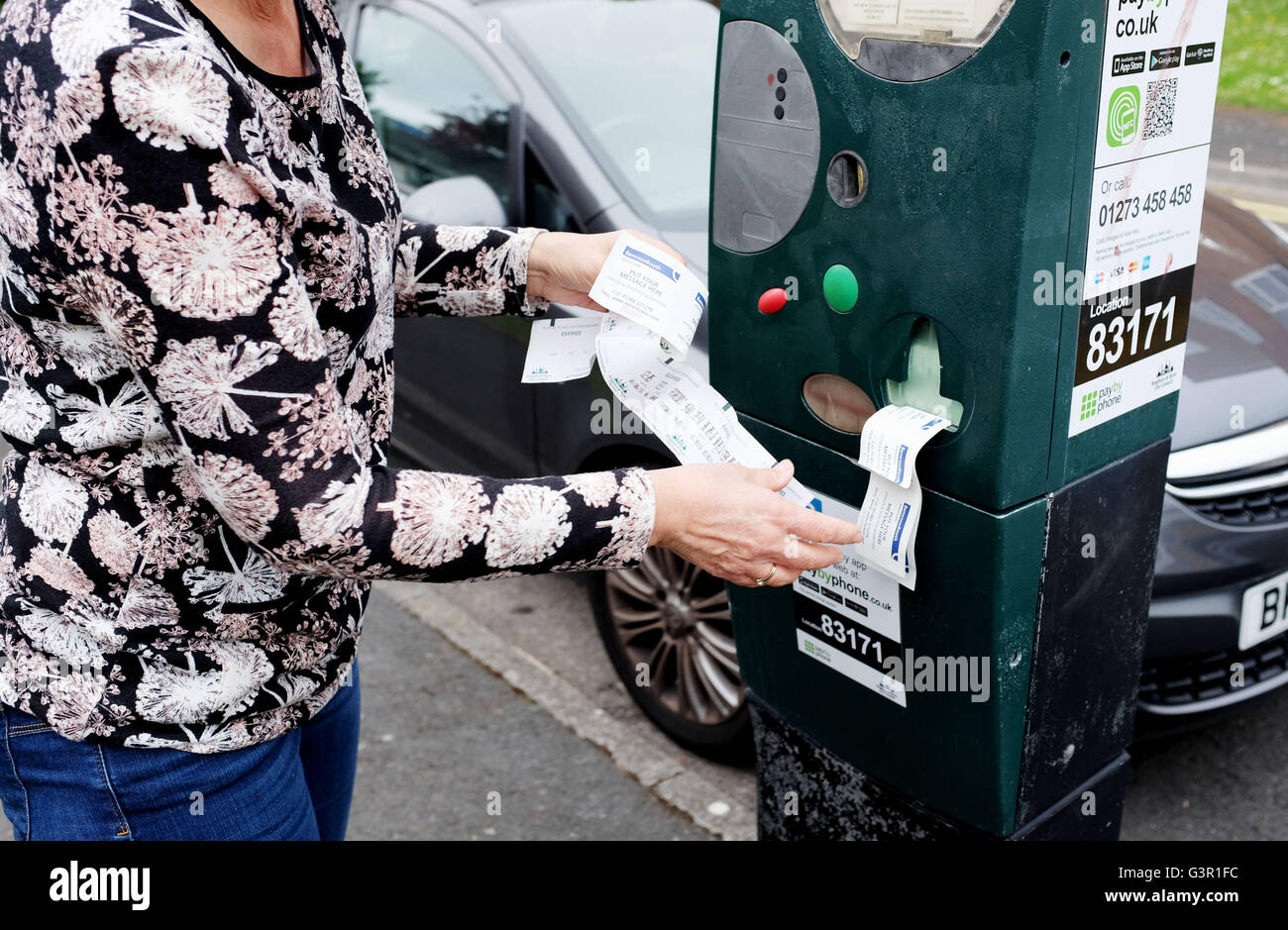 Broken parking meter in city of Brighton printing out useless tickets with frustrated female motorist UK Stock Photo
