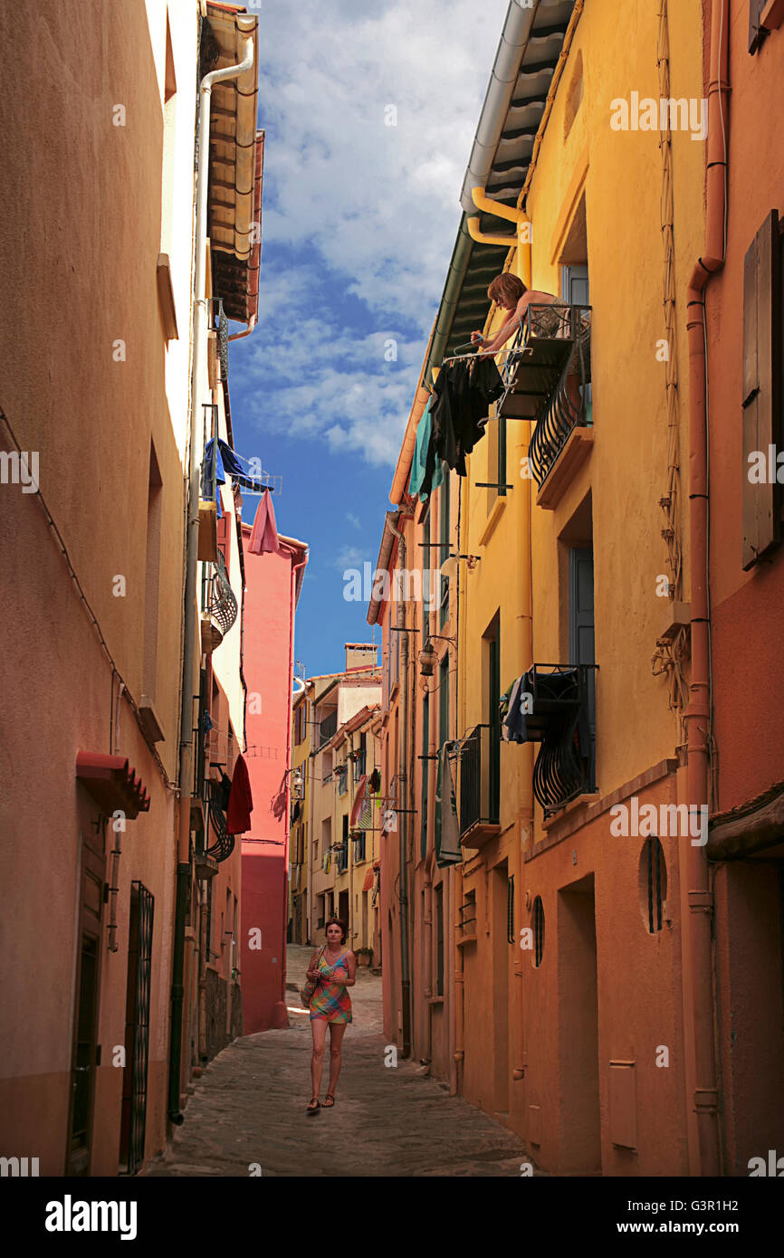 Girl in a brightly-coloured minidress walks down a narrow street, Collioure, Pyrénées-Orientales, Occitanie, - Stock Image