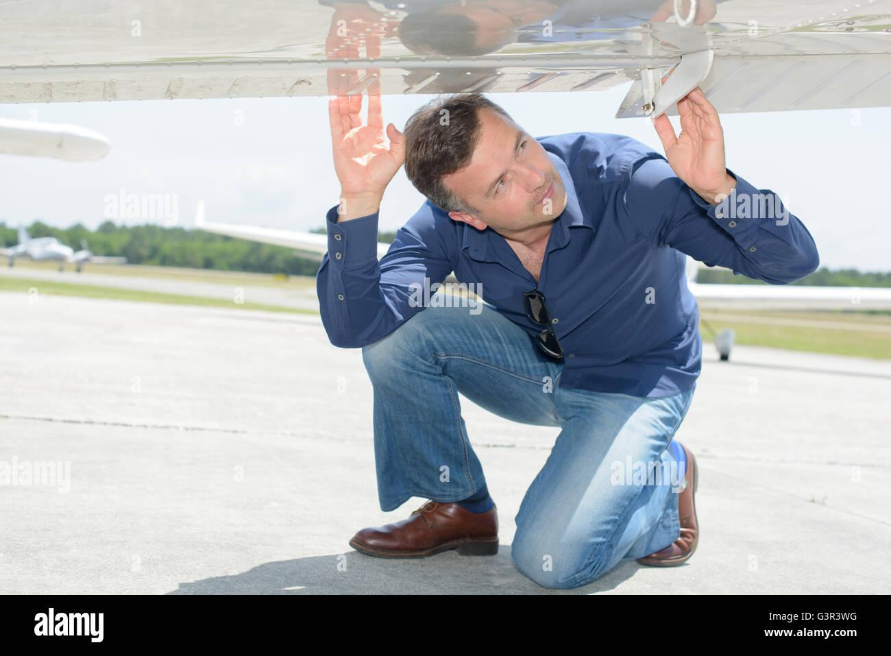 Man looking at underside of aircraft - Stock Image