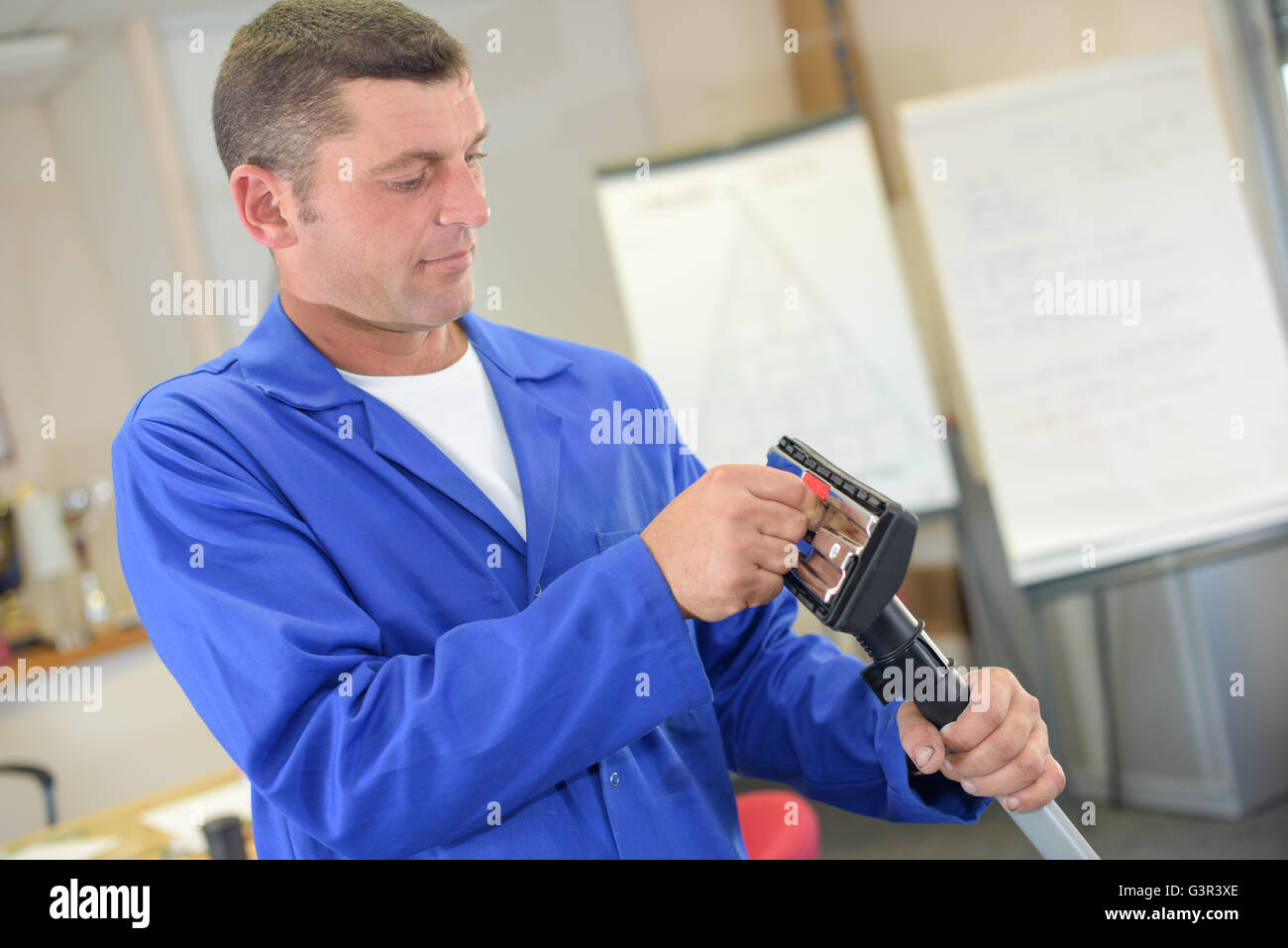 Man cleaning out vacuum attachment - Stock Image