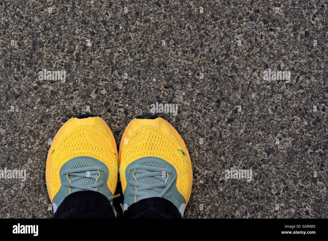 Worn out bright orange Nike running shoes against concrete background. - Stock Image