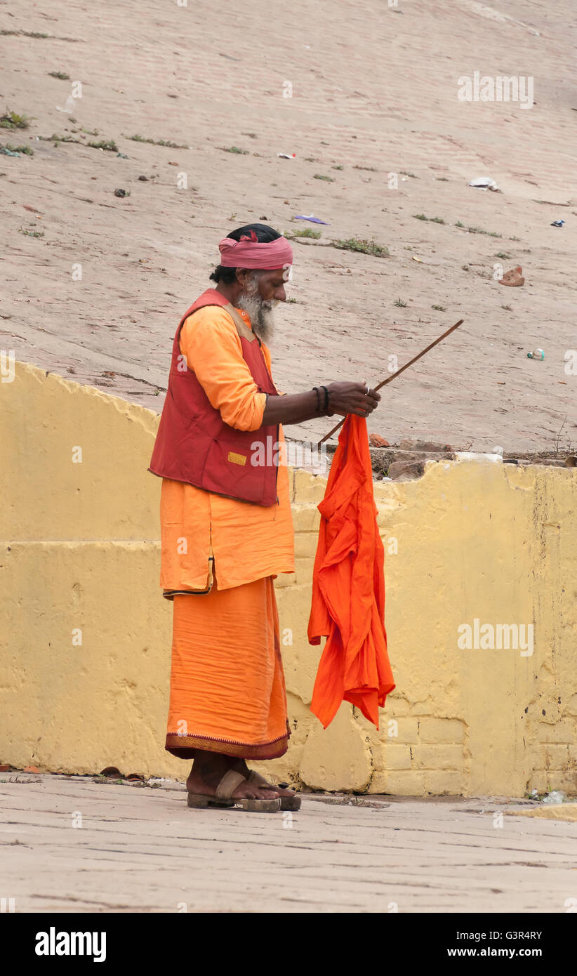 Unidentified Indian Sadhu on ghat near sacred river Ganges in Varanasi. Uttar Pradesh, India - Stock Image