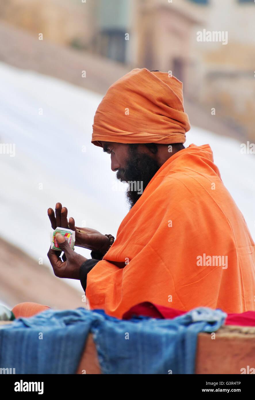Unidentified Indian Sadhu on ghat near sacred river Ganges in Varanasi. Uttar Pradesh, India - Stock Image
