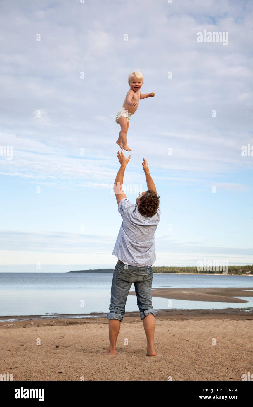 Sweden, Medelpad, Juniskarr, Man throwing son (2-3) in air - Stock Image