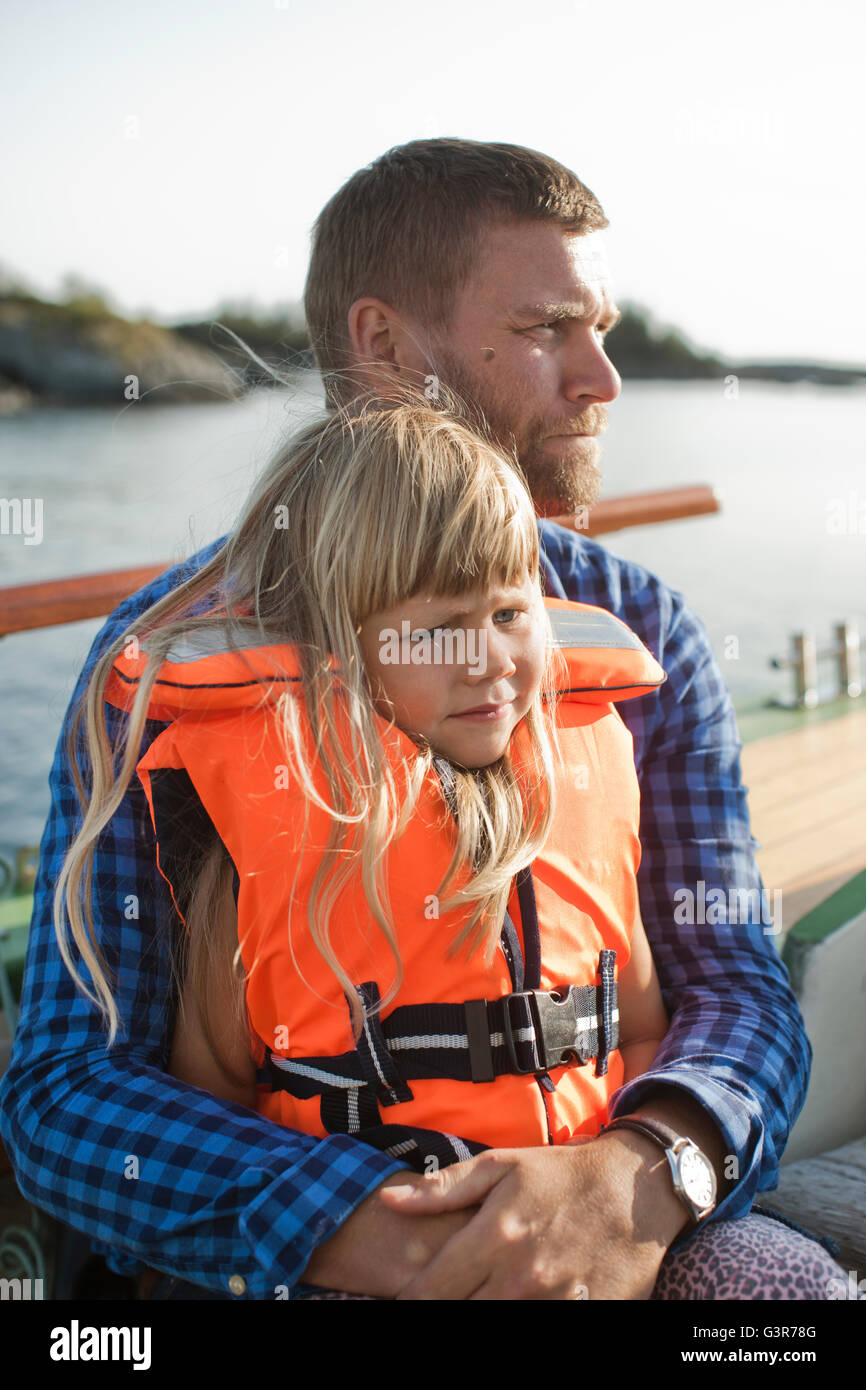 Norway, Bergen, Girl (4-5) in life jacket sitting on father´s laps - Stock Image