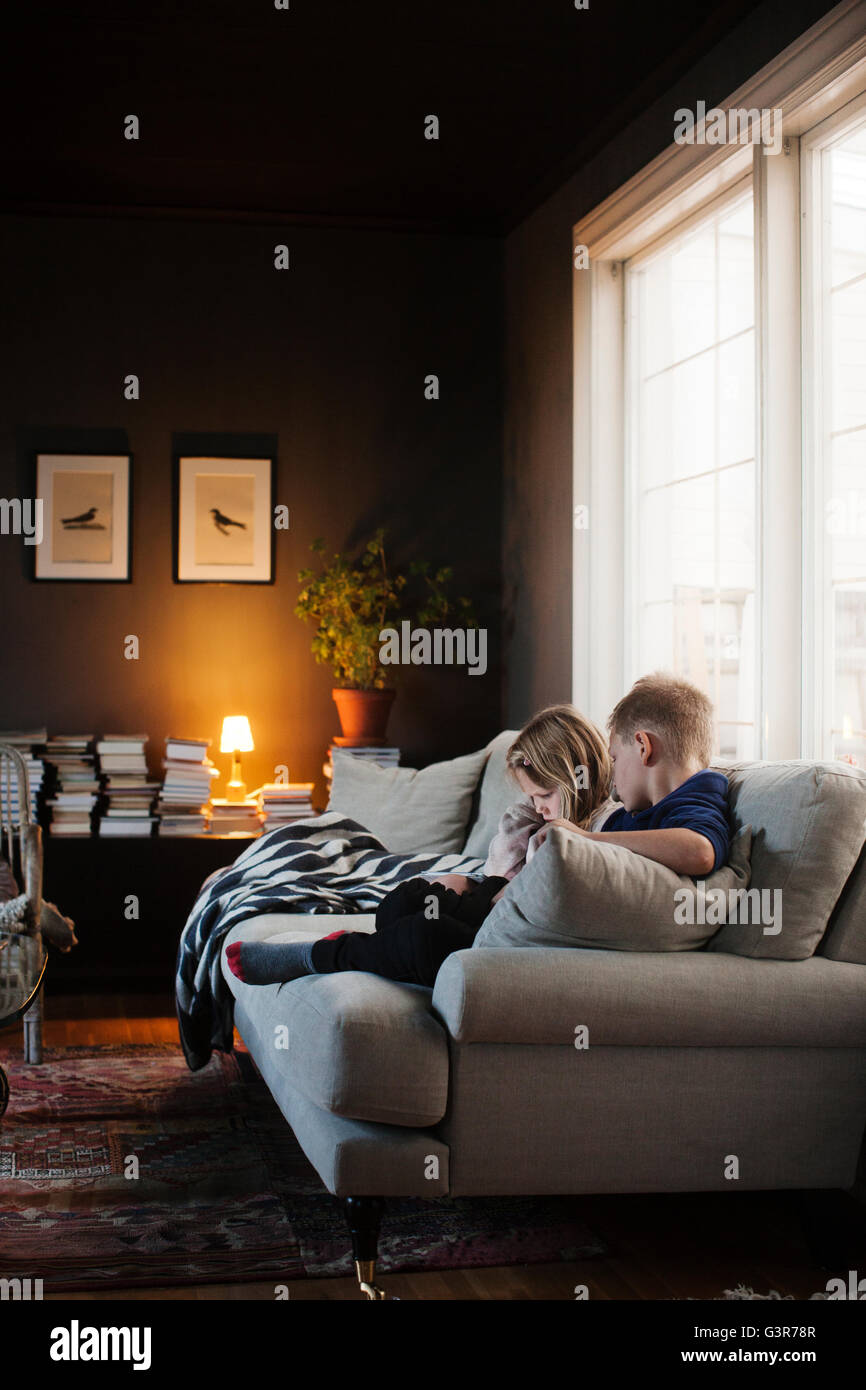 Denmark, Boy (8-9) and girl (4-5) sitting on sofa in living room - Stock Image