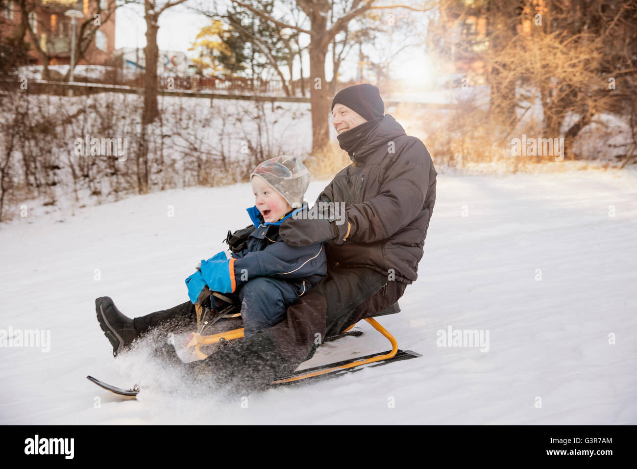 Sweden, Sodermanland, Johanneshov, Father with son (4-5) tobogganing - Stock Image