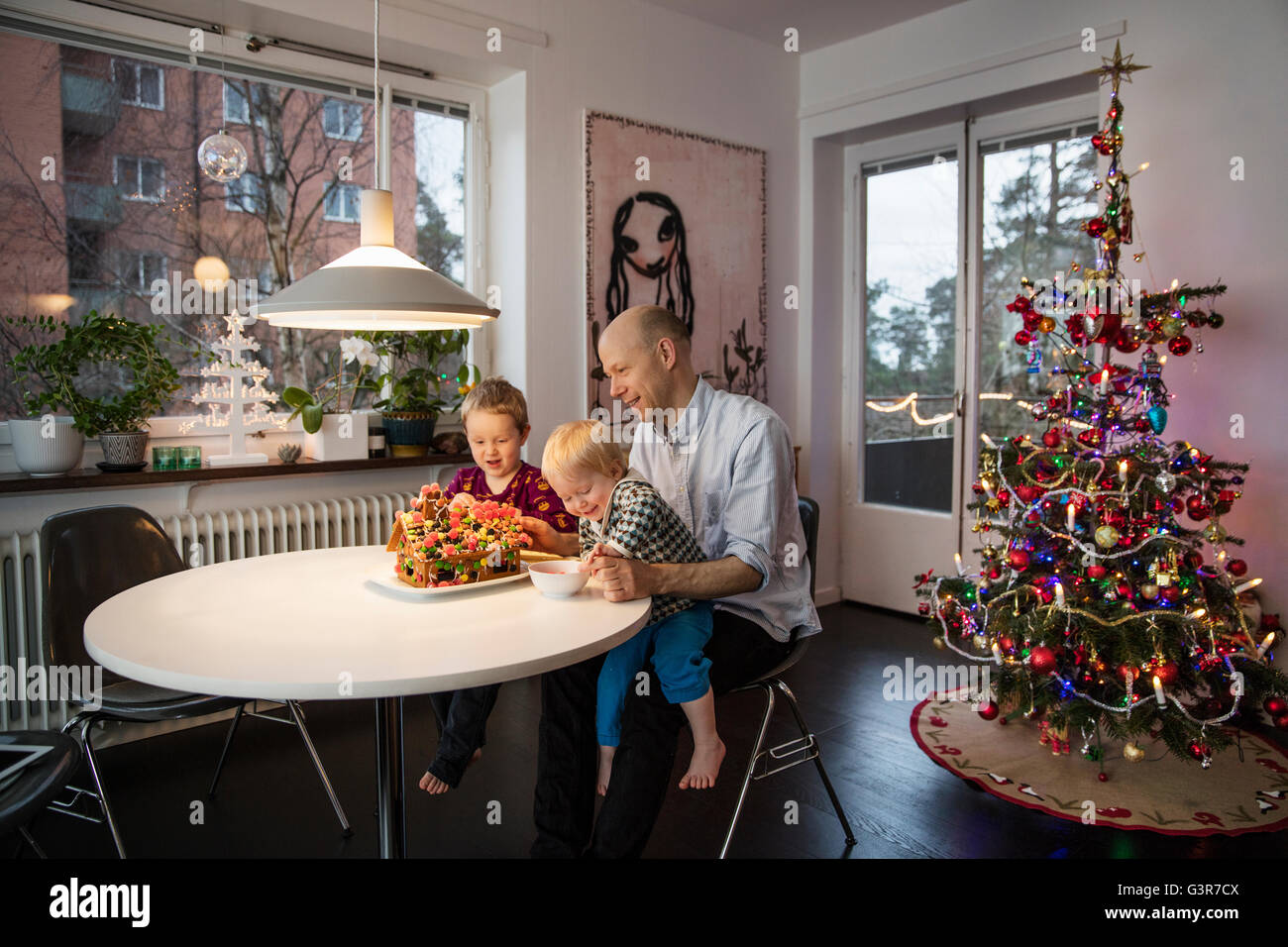 Sweden, Man and two boys (18-23 months, 4-5) decorating gingerbread house - Stock Image