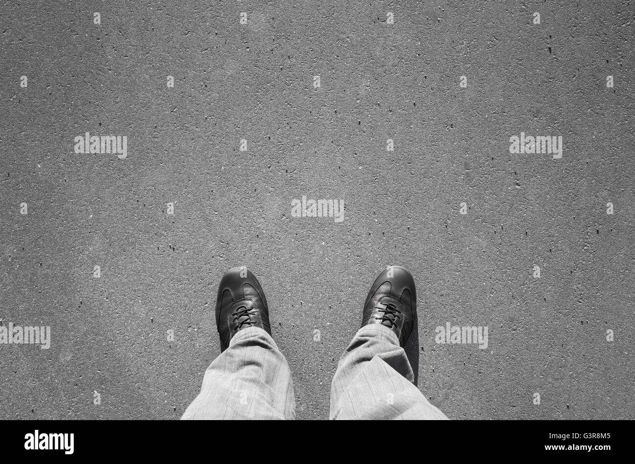 Male feet in black new shining leather shoes standing on urban asphalt pavement - Stock Image