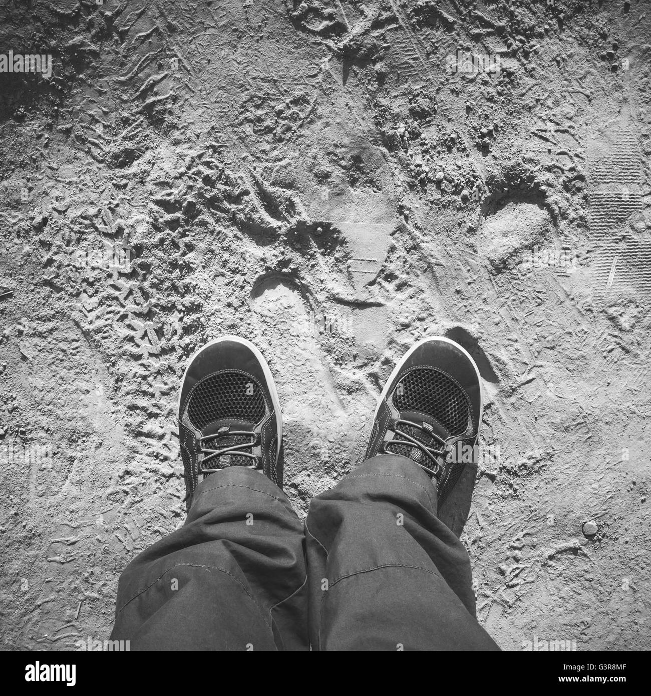 Male feet in sporty shoes stand on dirty dusty road, first person view, square black and white photo - Stock Image