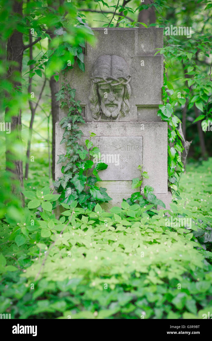 A grave with Christ's face on its headstone in the Kerepesi Cemetery in the Jozsefvaros area of Budapest overgrown - Stock Image