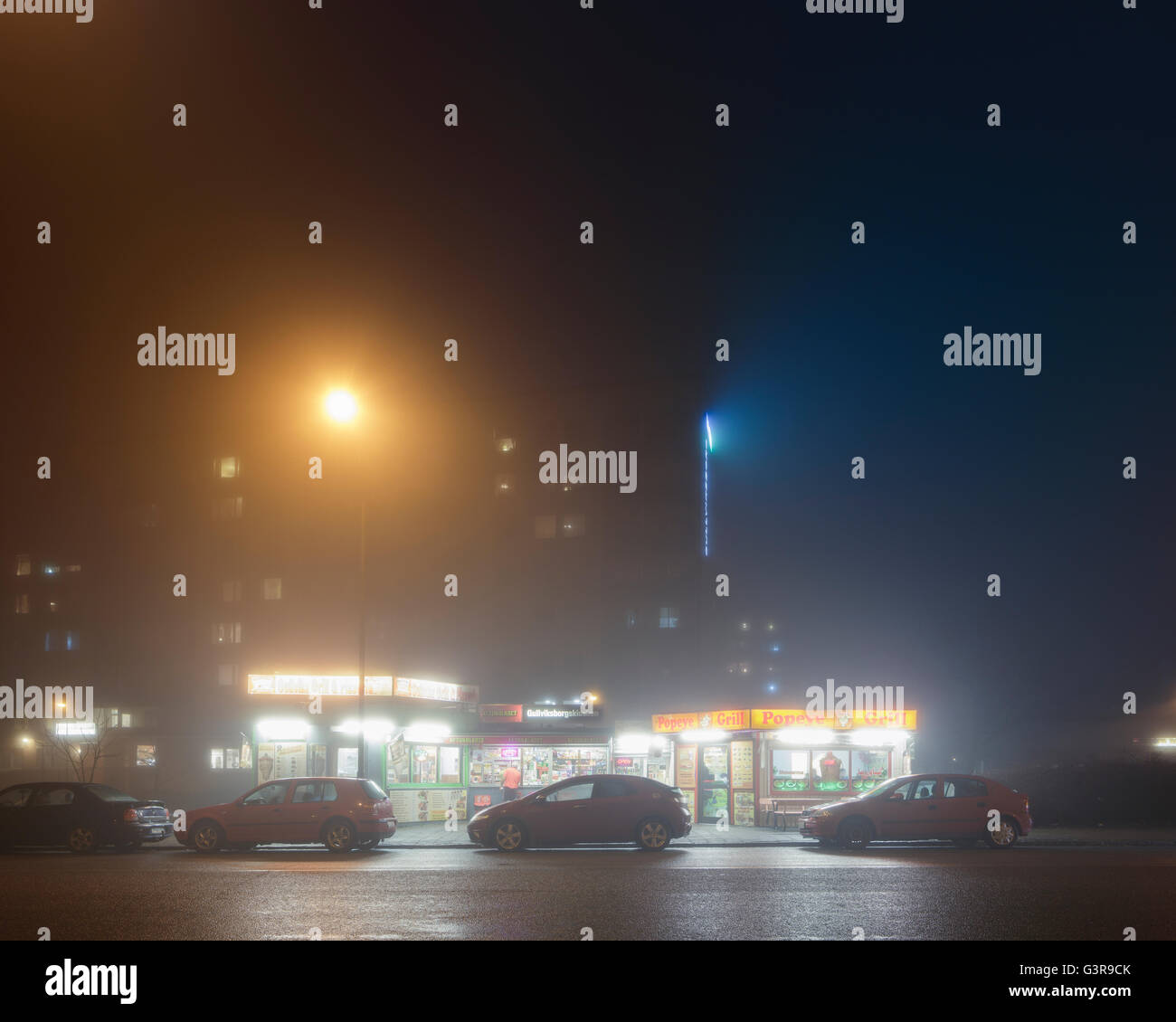 Sweden, Skane, Malmo, Gullviksborg, Cars parked by small stores at night - Stock Image