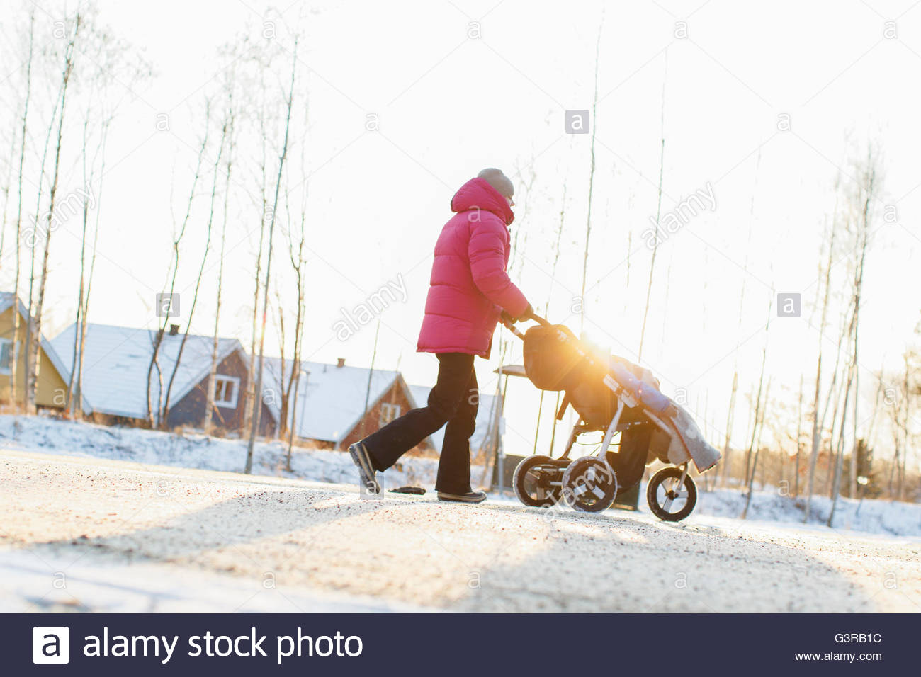 Sweden, Sodermanland, Jarna, Mother pushing boy (2-3) in stroller - Stock Image