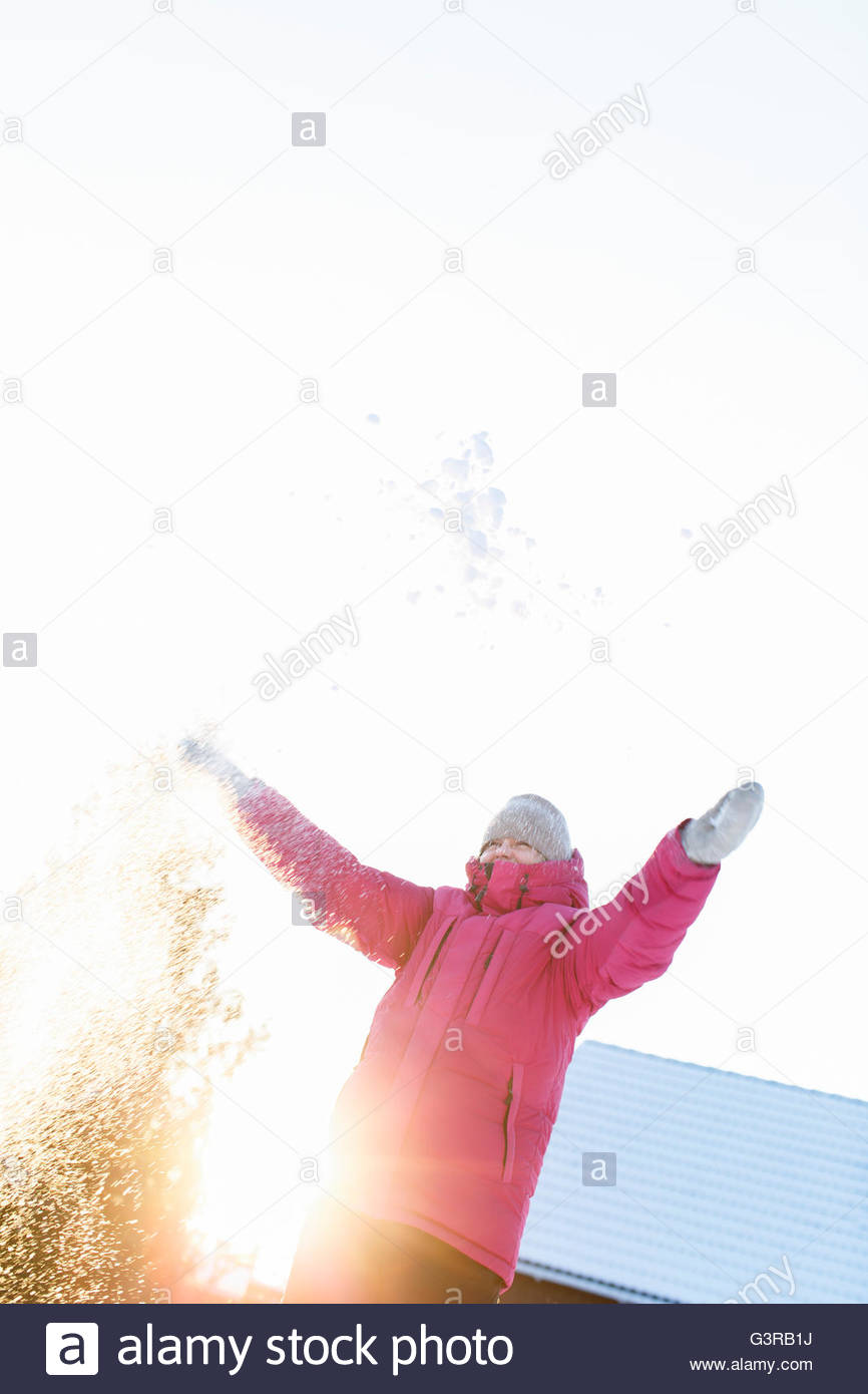 Sweden, Sodermanland, Mid-adult woman throwing snow - Stock Image
