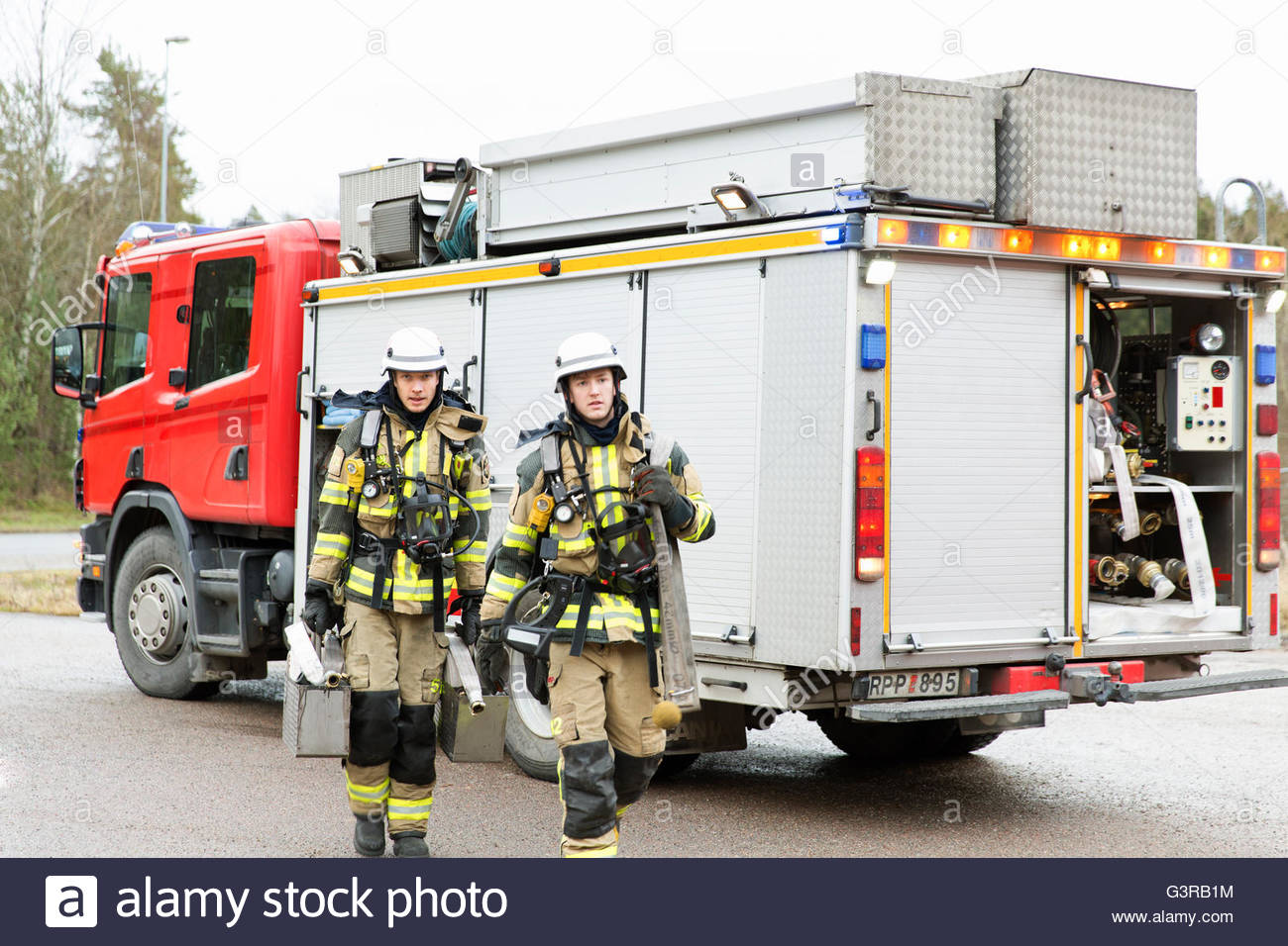 Sweden, Sodermanland, Fire-fighters by fire engine - Stock Image