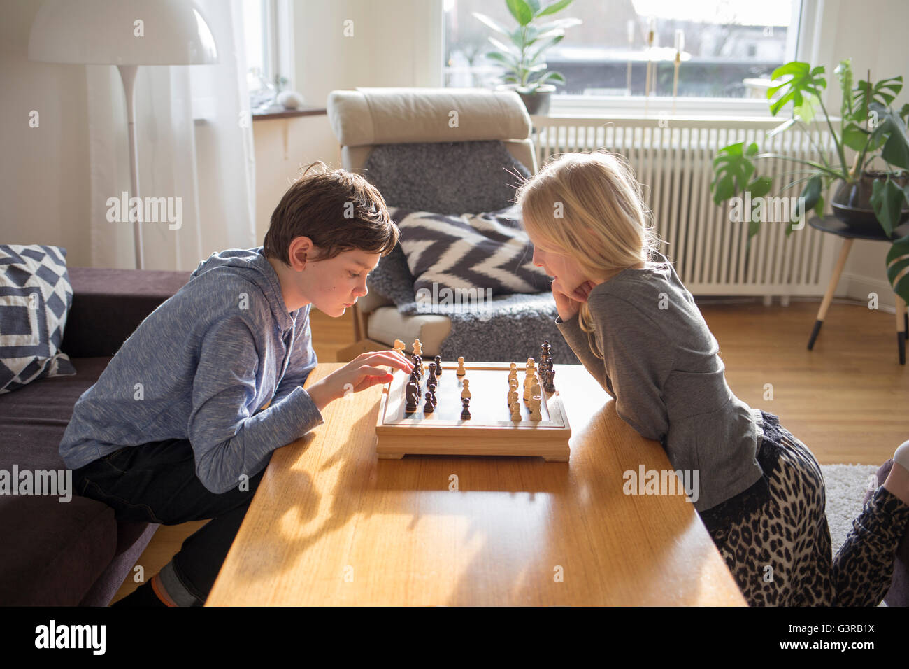 Sweden, Boy (12-13) and girl (10-11) playing chess in living room - Stock Image