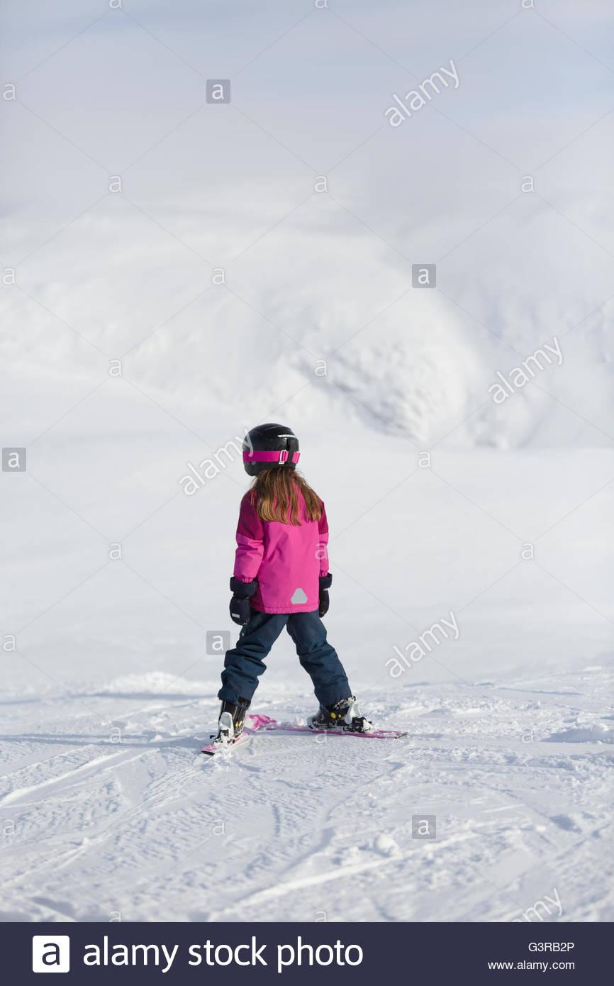Sweden, Vasterbotten, Hemavan, Little girl (6-7) in ski wear standing on mountain slope Stock Photo