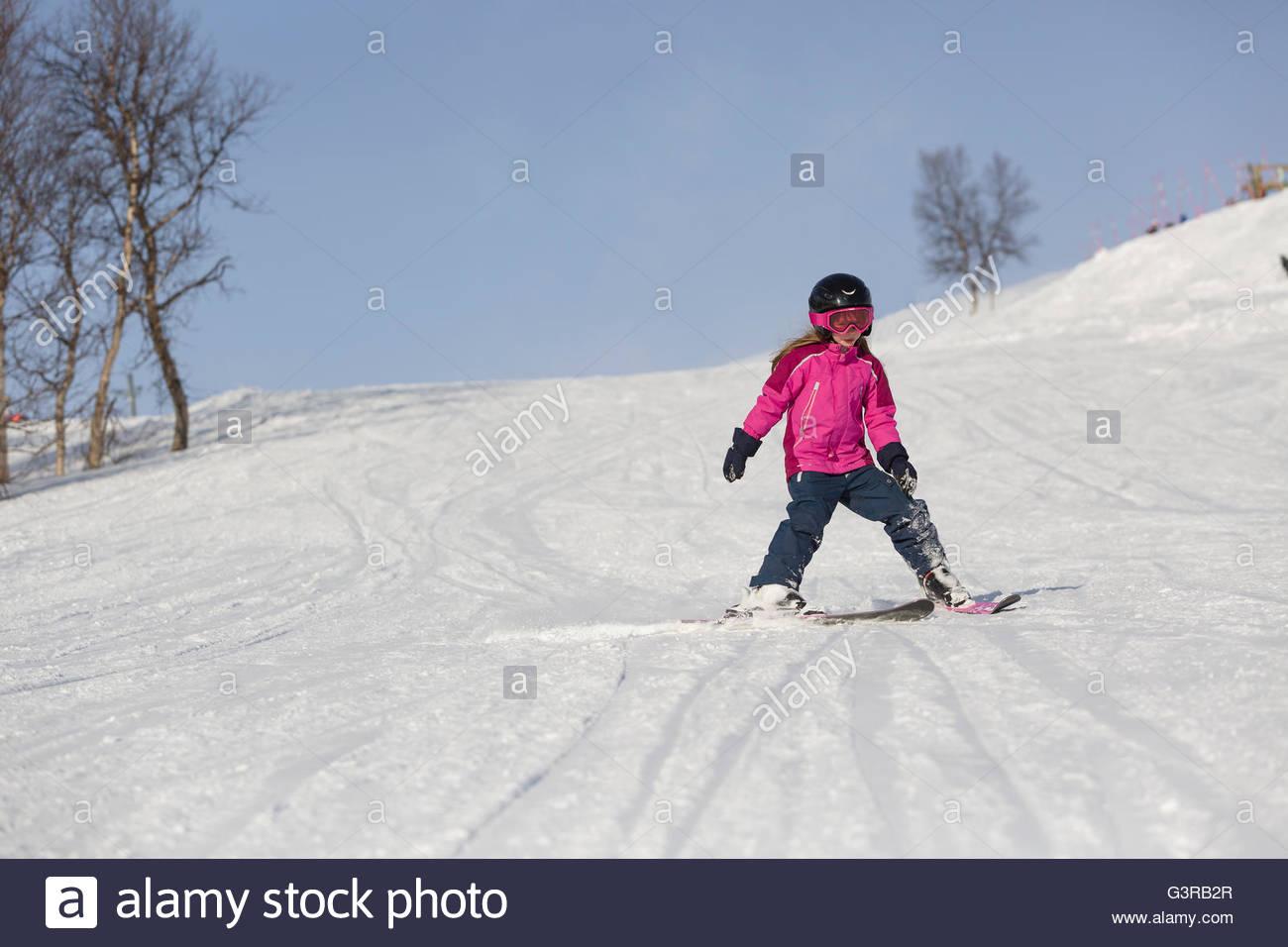 Sweden, Vasterbotten, Hemavan, Little girl (6-7) in ski wear sliding along mountain slope Stock Photo