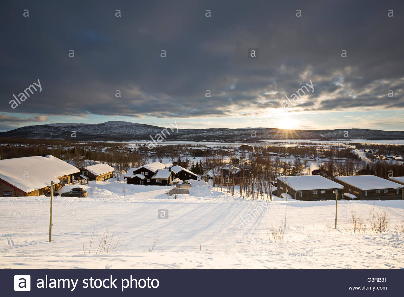 Sweden, Vasterbotten, Hemavan, Wooden houses at ski resort at sunset - Stock Image