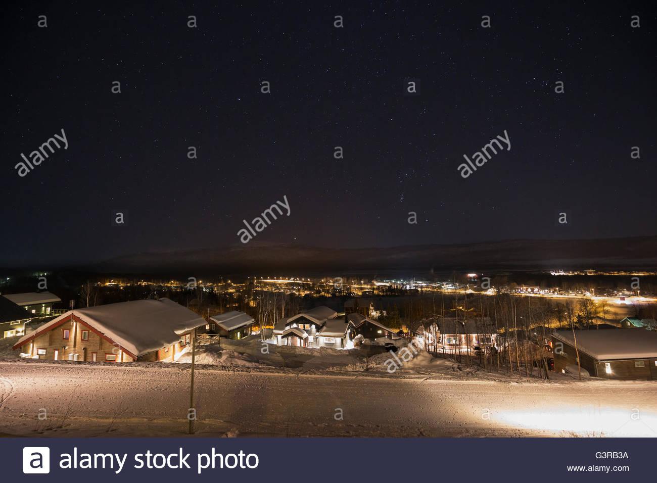 Sweden, Vasterbotten, Hemavan, Wooden houses at ski resort at night - Stock Image