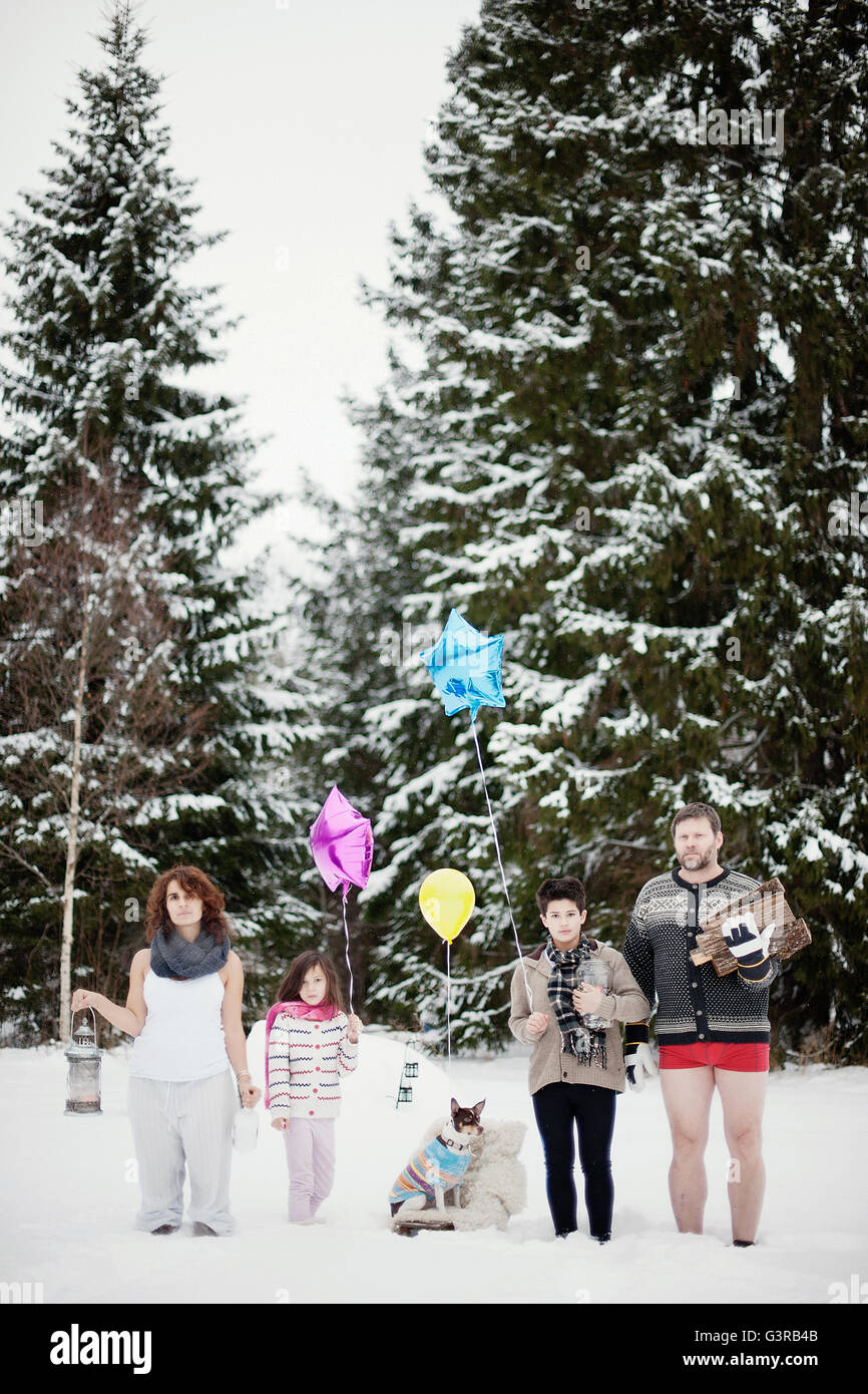 Sweden, Vastmanland, Bergslagen, Family with two children (6-7, 10,11) in winter forest during christmas - Stock Image