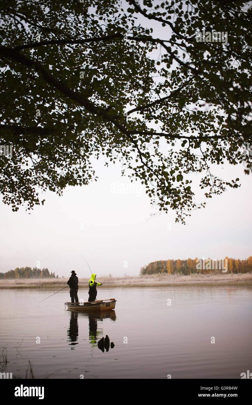 Sweden, Vastmanland, Bergslagen, Torrvarpen, Young men fishing in lake at sunset - Stock Image