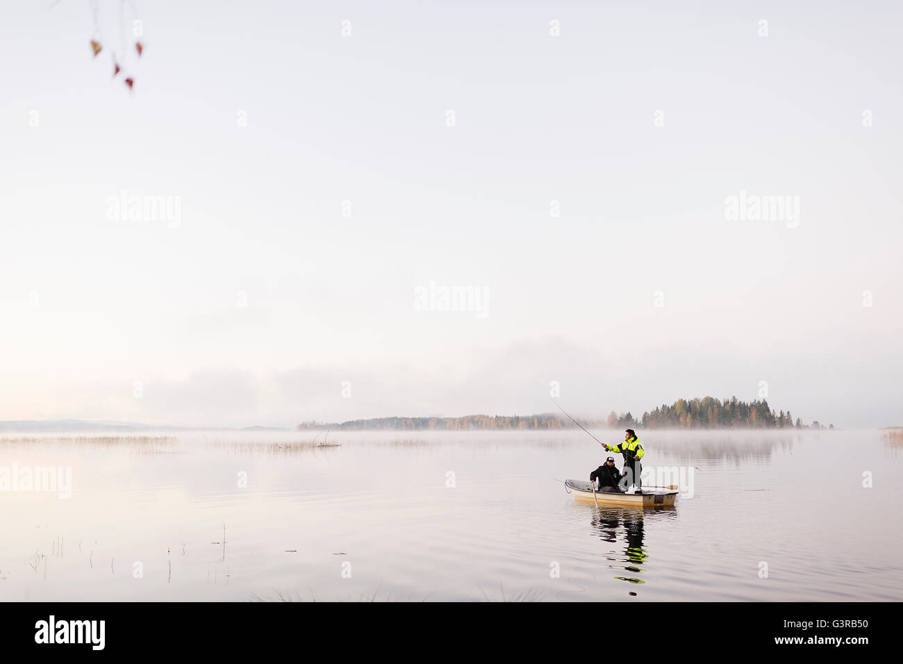 Sweden, Vastmanland, Bergslagen, Torrvarpen, Young men fishing in lake at sunset - Stock Image