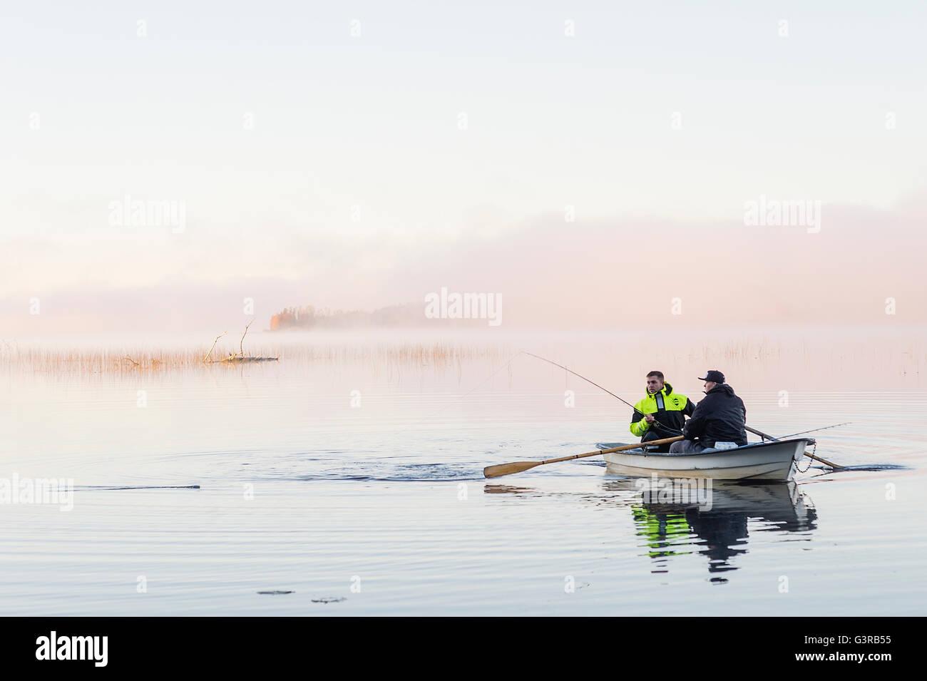 Sweden, Vastmanland, Bergslagen, Torrvarpen, Young men fishing in lake at sunset Stock Photo